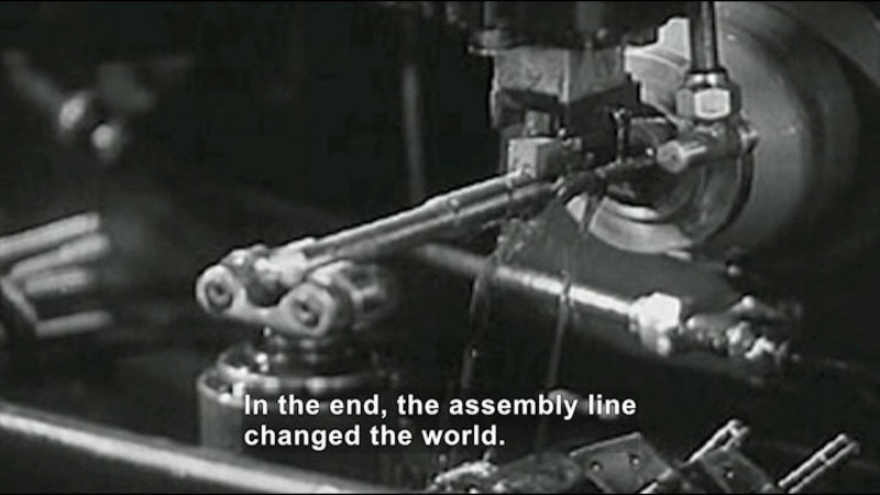 Black and white photo of a complex machine. Caption: In the end, the assembly line changed the world.