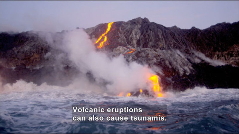 Lava from a volcano cooling as it hits a body of water. Caption: Volcanic eruptions can also cause tsunamis.