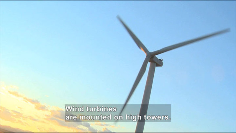 Three blade wind turbine as seen from below. Caption: Wind turbines are mounted on high towers.