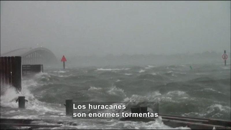 A hurricane's waves flooding a road. Spanish captions.