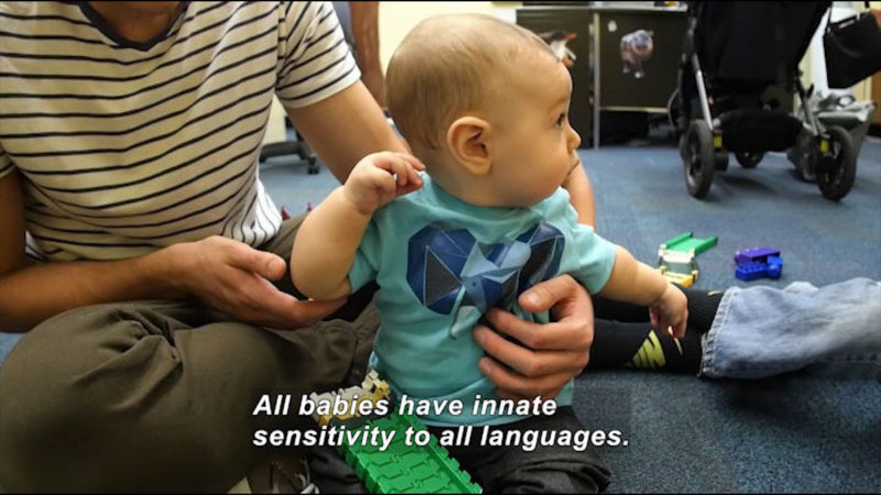 A parent sitting with their baby. Caption: All babies have innate sensitivity to all languages.