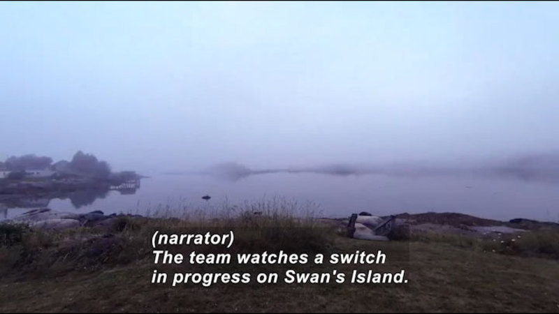 Fog rising off a lake. Caption: (narrator) The team watches a switch in progress on Swan's Island.