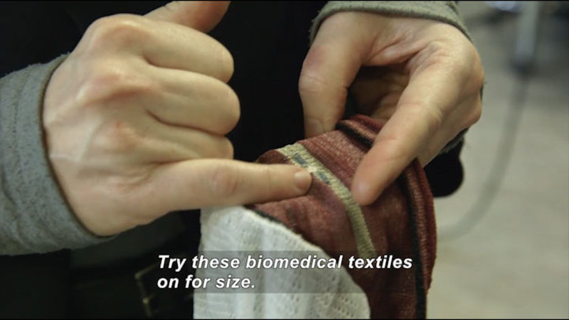 Person pointing at fabric. Caption: Try these biomedical textiles on for size.